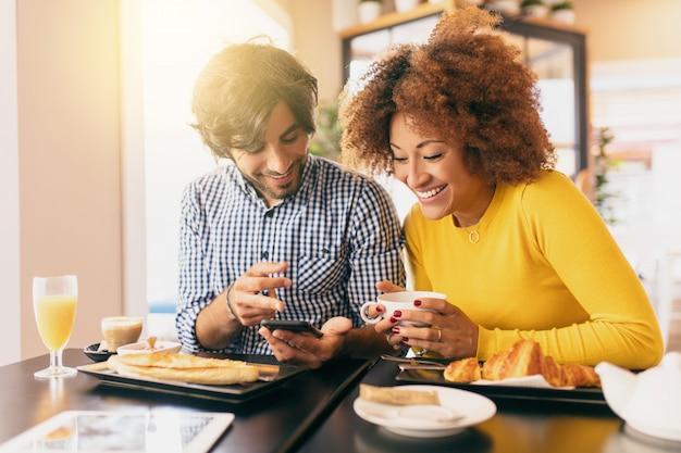 Jovem casal moderno no café, ela está bebendo um chá e ele está bebendo um café