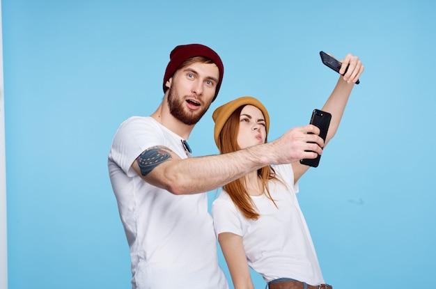 Jovem casal morto em camisetas com telefones em suas mãos tecnologia moderna