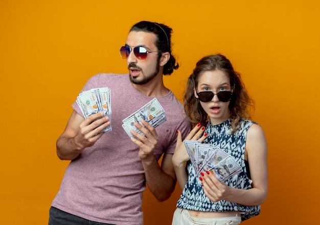 Jovem casal mostrando dinheiro em pé sobre uma parede laranja