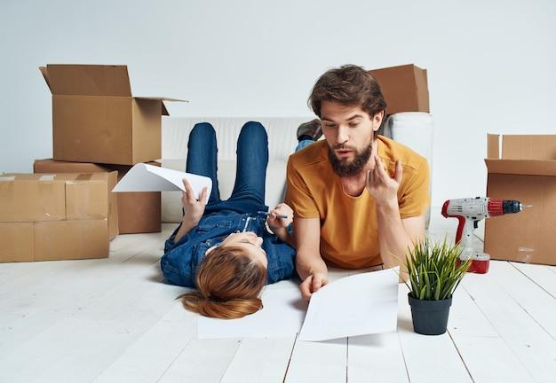 Jovem casal movendo caixas de renovação para inauguração de casa
