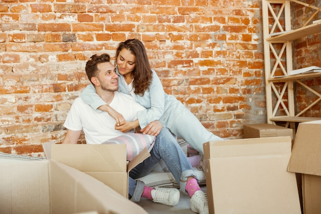 Jovem casal mudou-se para uma nova casa ou apartamento. deitados juntos, acariciando, abraçando, se divertindo no dia da mudança. pareça feliz, sonhador e confiante. família, mudança, relações, primeiro conceito de casa.
