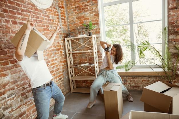 Jovem casal mudou-se para uma nova casa ou apartamento. divertir-se com caixas de papelão, relaxar após limpar e desfazer as malas no dia da mudança