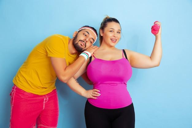 Jovem casal muito caucasiano com roupas brilhantes, treinando no espaço azul. conceito de esporte, emoções humanas, expressão, estilo de vida saudável, relação, família
