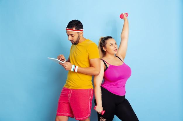Jovem casal muito caucasiano com roupas brilhantes, treinando sobre fundo azul conceito de esporte, emoções humanas, expressão, estilo de vida saudável, relação, família. ela está treinando, ele está usando tablet.