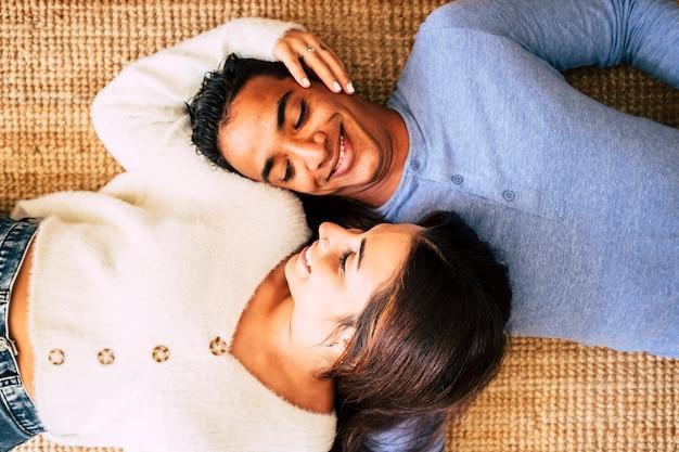 Jovem casal muito interracial deita-se no tapete e sorri tendo carinho e amor com cada um.