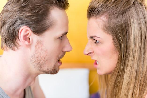 Jovem casal, mulher e homem, em luta furiosa olhando para um