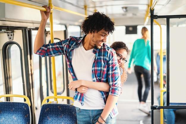 Jovem casal multicultural abraçando no transporte público.