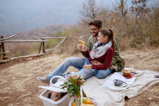 Jovem casal multicultural apaixonado sentado no cobertor no piquenique e desfrutando de champanhe. tempo de outono.