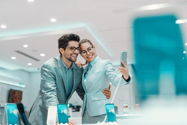 Jovem casal multicultural atraente vestido elegante tomando selfie com novo telefone inteligente na loja de tecnologia.