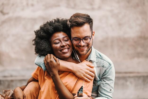 Jovem casal multicultural fofo apaixonado, abraçando e ouvindo música juntos sobre fones de ouvido.