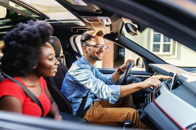 Jovem casal multicultural fofo sentado em um carro e se preparando para dirigir.