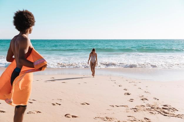 Jovem casal multiétnica relaxante na praia