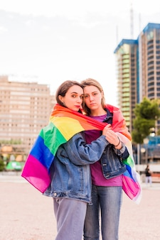 Jovem casal multiétnico de lésbicas com um conceito de diversidade de bandeira de arco-íris