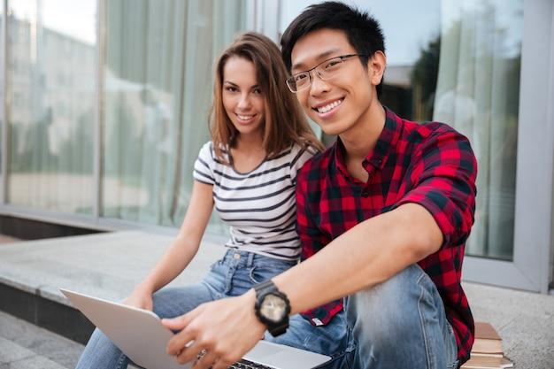Jovem casal multiétnico e alegre conversando e usando laptop juntos ao ar livre
