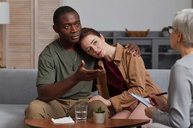 Jovem casal multiétnico se apoiando enquanto faz uma consulta com um psicólogo
