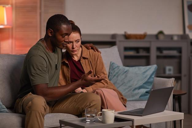 Jovem casal multiétnico sentado no sofá em frente ao laptop e conversando online em casa