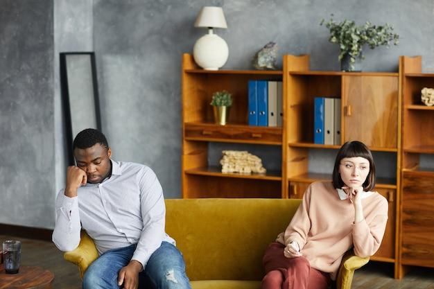 Jovem casal multiétnico sentado no sofá separadamente, eles estão brigando e sentados no consultório do psicólogo