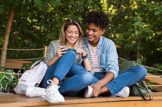 Jovem casal multiétnico sorridente conversando