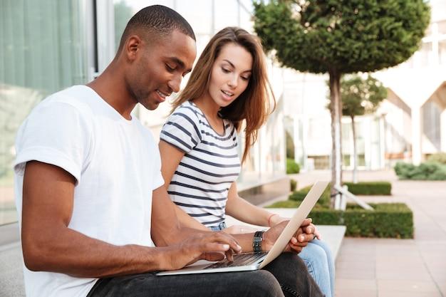 Jovem casal multiétnico usando laptop juntos ao ar livre