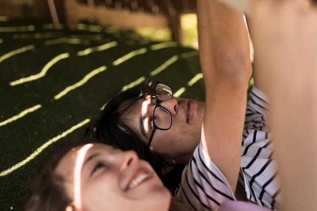 Jovem casal multirracial com as mãos levantadas, deitado na sombra