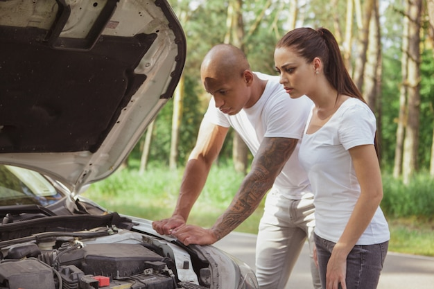 Jovem casal multirracial com um carro quebrado no meio da estrada