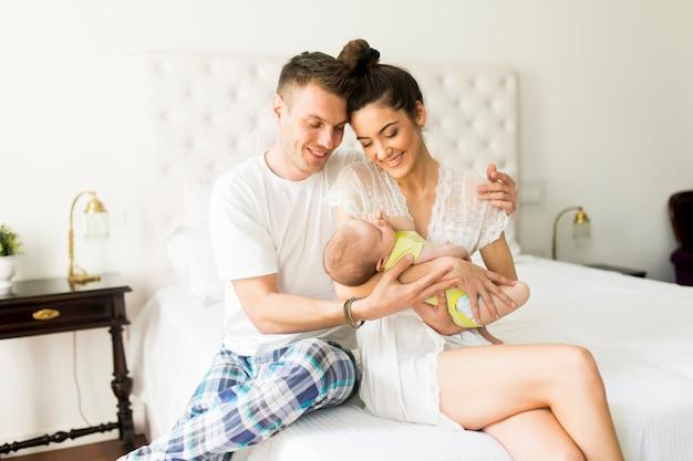 Jovem casal na cama com o bebê