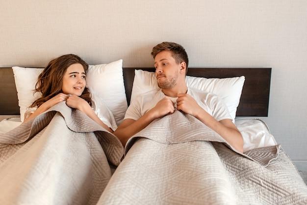 Jovem casal na cama. medo de sexo, mulher tímida e homem escondido debaixo do cobertor antes da intimidade
