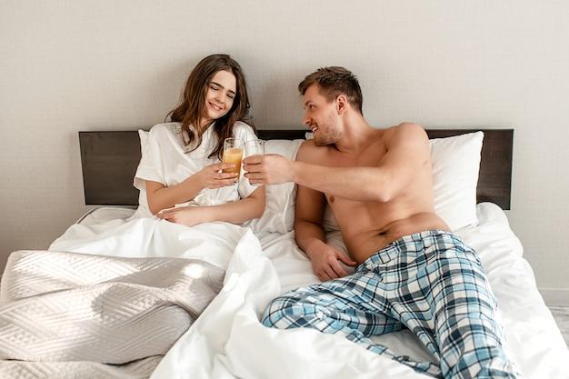 Jovem casal na cama. sorrindo, homem e mulher de pijama com suco saudável, bom dia