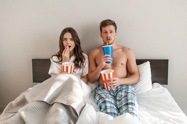 Jovem casal na cama. um intrigado homem e mulher bonita estão comendo pipoca e assistindo tv juntos no quarto