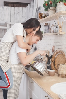 Jovem casal na cozinha. homem e mulher cozinhando. namorado e namorada dentro de casa na cozinha.