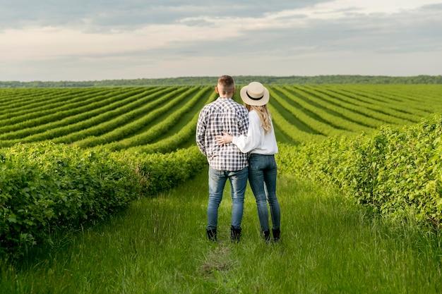 Jovem casal na fazenda, admirando a vista