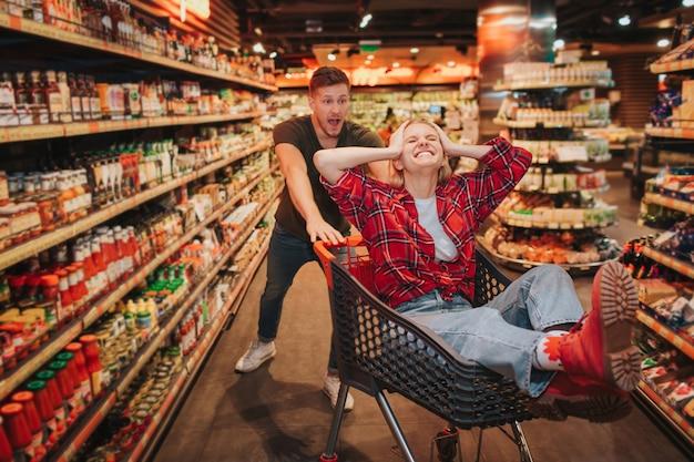 Jovem casal na mercearia. eles brincam juntos. mulher sente-se no carrinho e mantenha os olhos fechados. o cara grita para trás e solta o carrinho. diversão e felicidade.