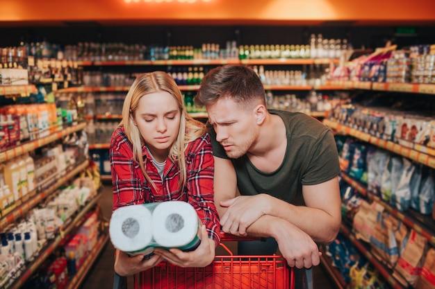 Jovem casal na mercearia escolhendo papel higiênico