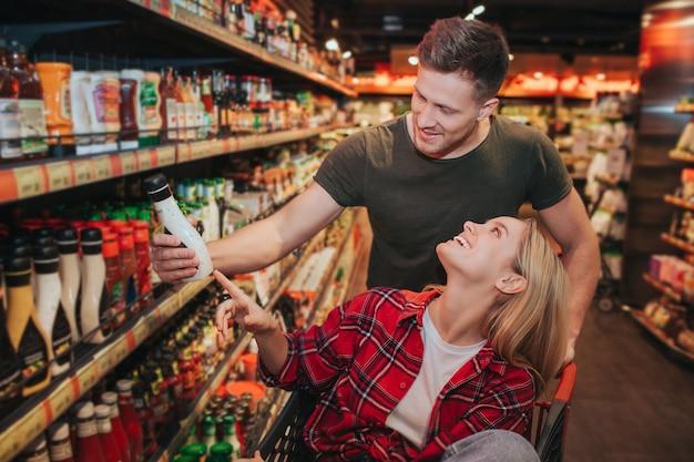 Jovem casal na mercearia, escolher molho