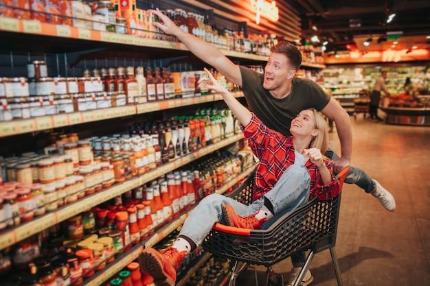 Jovem casal na mercearia. mulher e homem feliz apontam na prateleira de molho. ela senta no carrinho e se diverte. compra de produtos na loja.