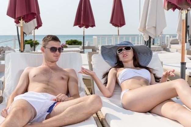 Jovem casal na moda verão praia, conversando enquanto descansava em espreguiçadeiras em um resort em um clima ensolarado.