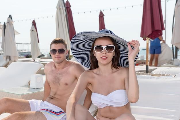 Jovem casal na praia de verão usa óculos de sol, olhando para a câmera enquanto está sentado em espreguiçadeiras em um resort.