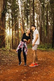 Jovem casal na selva. os turistas percorrem a selva. eles olham para as árvores e o sol brilha. conceito de turismo e viagens.