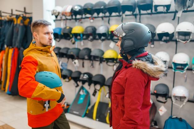 Jovem casal na vitrine experimentando capacetes para esqui ou snowboard, vista lateral, loja de esportes.