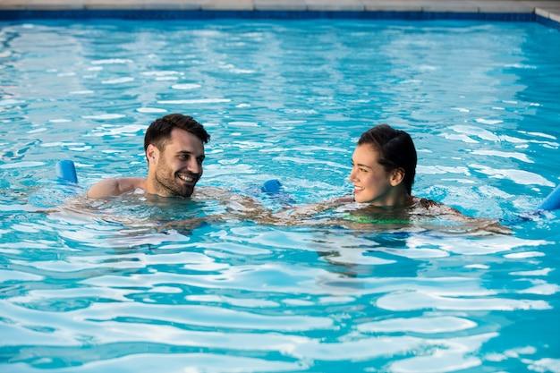 Jovem casal nadando com tubos infláveis na piscina