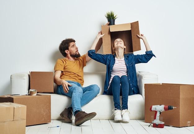 Jovem casal nas caixas de inauguração da sala com coisas em movimento