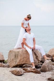 Jovem casal nas rochas no mar