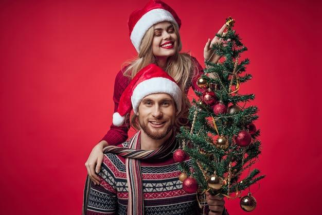 Jovem casal natal feriado diversão romance fundo vermelho. foto de alta qualidade