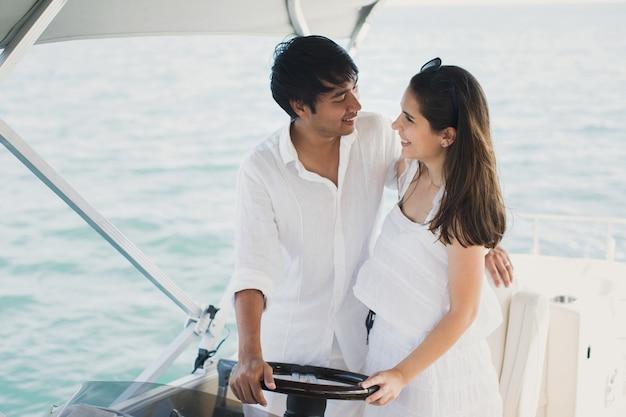 Jovem casal navegando em um iate no oceano índico