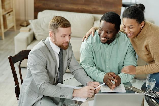 Jovem casal negro com consultor de empréstimo sentado à mesa, tendo ajuda profissional em hipotecas imobiliárias