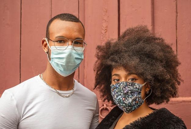 Jovem casal negro com máscara protetora