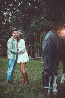 Jovem casal no abraço no pasto com cavalos