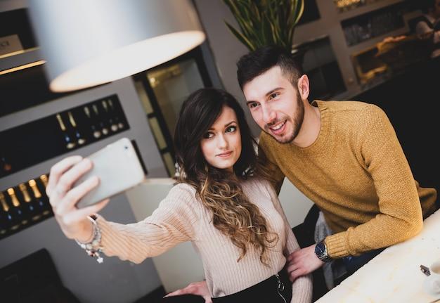 Jovem casal no bar tomando um selfie.