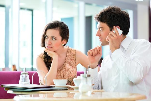 Jovem casal no café não interagindo, mas no telefone