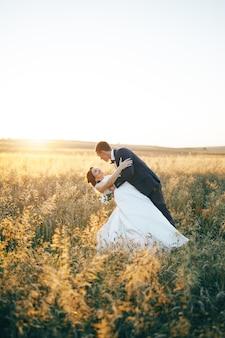 Jovem casal no campo de trigo por do sol